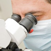 Dr Rammo looking into microscope, justSMILE Ramsgate Sydney NSW